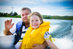 Travel of children on water in the boat. Water walk of family by the boat on the river in a sunny day stock image