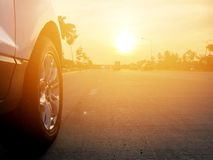 Travel. Close up the front wheel of white car parked the roadside on cement road. Wide view in the evening light and orange light. Selective focus. Copy space or Stock Photos