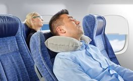 Man sleeping in plane with cervical neck pillow. Travel, comfort and people concept - men sleeping in plane with inflatable cervical neck pillow over porthole Stock Photo