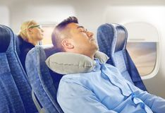 Man sleeping in plane with cervical neck pillow. Travel, comfort and people concept - men sleeping in plane with inflatable cervical neck pillow over porthole Stock Image