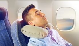 Man sleeping in plane with cervical neck pillow. Travel, comfort and people concept - men sleeping in plane with inflatable cervical neck pillow over porthole Stock Photography