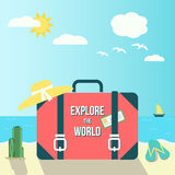 Travel composition with a suitcase on the sand, leisure items and the sea with the sun and gulls in the background. Royalty Free Stock Image