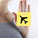 TRAVEL CONCEPT. Adhesive note with plane shape taped on woman hand Royalty Free Stock Photo