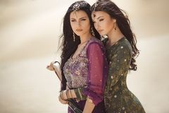 Travel concept. Two gordeous women sisters traveling in desert. Arabian girls. royalty free stock photo