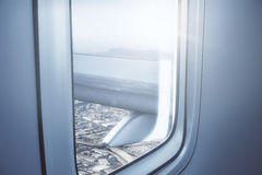 Travel concept. Airplane wing on city and sky background. View from illuminator. Travel concept. 3D Rendering Stock Photography