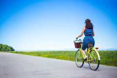 Travel concept - back view of woman riding vintage bicycle with Stock Photo