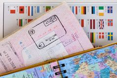 Travel concept background with map, passport with customs entry stamps and colorful national flags.  royalty free stock images