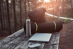 Travel concept. Backpack, tourist mat, laptop, smartphone and thermos bottle on a wooden table in beautiful forest. Royalty Free Stock Images