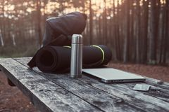 Travel concept. Backpack, tourist mat, laptop, smartphone and thermos bottle on a wooden table in beautiful forest. Royalty Free Stock Photo