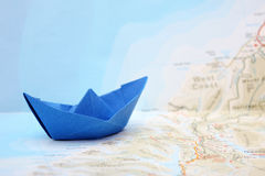 Travel concept - blue folded paper boat on map Stock Photo