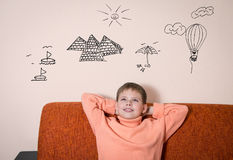 Travel concept. Boy sitting on sofa dreaming about vacation. Child dreaming of traveling. Stock Photo