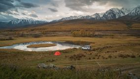 Camping, tent and car on the shore of a mountain lake on the sunrise background. Travel concept: Camping, tent and suv offroad car on the shore of a mountain stock video