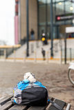 Travel concept of child backpack on bench of train station Stock Image