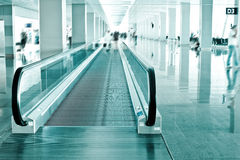 Travel concept. Escalator inside modern airport terminal. Image in blue colors with blur Royalty Free Stock Photography