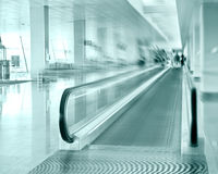 Travel concept. Escalator inside modern airport terminal. Image in blue colors with blur Royalty Free Stock Photo