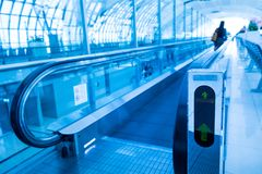 Travel concept. Escalator walk way inside modern airport termina. L. Image in blue colors Royalty Free Stock Image
