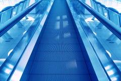 Travel concept. Escalator walk way inside modern airport termina. L. Image in blue colors Stock Photos