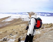 Travel concept. Female hiker with backpack enjoing view of Lake Baikal, Siberia, Russia. Winter tourism. Royalty Free Stock Photography