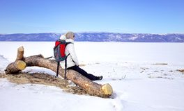 Travel concept. Female hiker with backpack enjoing view of Lake Baikal, Siberia, Russia. Winter tourism. stock photos