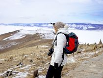 Travel concept. Female hiker with backpack enjoing view of Lake Baikal, Siberia, Russia. Winter tourism. royalty free stock images