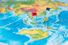 Travel concept with flag pushpins and world map.  Royalty Free Stock Photo