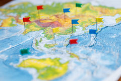 Travel concept with flag pushpins and world map.  Stock Image