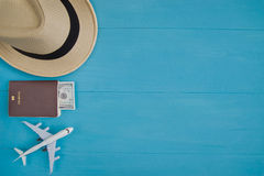 Travel Concept : Flat lay of straw hat, passport with money, plane model, on blue wooden background, with copy space.
