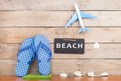 Flops, toy airplane, seashells and blackboard with inscription & x22;BEACH& x22;. Travel concept - flops, toy airplane, seashells and blackboard with inscription stock image