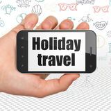 Travel concept: Hand Holding Smartphone with Holiday Travel on display. Travel concept: Hand Holding Smartphone with  black text Holiday Travel on display,  Hand Royalty Free Stock Photo