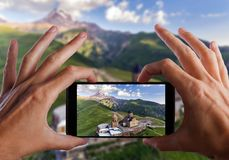 Travel concept. Hands making photo of Gergeti orthodox church high in the mountains, Georgia stock photo