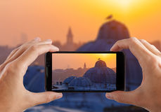 Travel concept. Hands making photo of night city with smartphone camera. Istanbul at sunset. Turkey Royalty Free Stock Photos