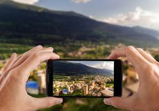 Travel concept. Hands making photo of Svaneti Old village in Georgia. Medieval tower. Mestia Royalty Free Stock Photography
