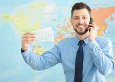 Travel concept. Handsome man talking by mobile phone. On map background Stock Photo