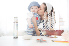 Travel concept. Happy sailor kid and mom playing indoors. Stock Photography