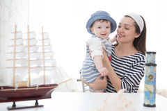 Travel concept. Happy sailor kid and mom playing indoors. Royalty Free Stock Images