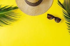 Travel concept: hat, palm leaf and sun glasses on yellow background. Top view, flat lay, space for text stock photos