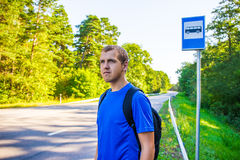Travel concept - hiker with backpack standing on bus stop on roa Stock Photo