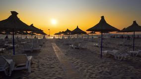 Umbrellas are close on the beach against sunset. Travel concept. The low season. All umbrellas are close on the beach against sunset. The period in the year when Stock Images