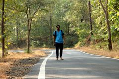 Travel concept man carrying backpack walking on the road passes through beautiful forests. In india Royalty Free Stock Image