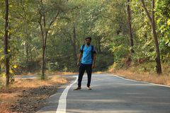 Travel concept man carrying backpack walking on the road passes through beautiful forests. In india Stock Photography