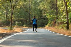 Travel concept man carrying backpack walking on the road passes through beautiful forests. In india Stock Images