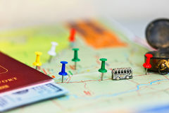 Travel concept - map with pins and accessories. Close up captured map with colored pushpins marking the destinations, tiny toy bus and travel accessories Stock Image