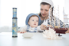 Travel concept. Mother and her baby boy playing with model of ship. Stock Photo