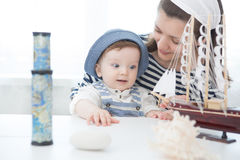Travel concept. Mother and her baby boy playing with model of ship. Travel concept. Mother and her baby boy are playing with a model of the ship. Mother and son Stock Image