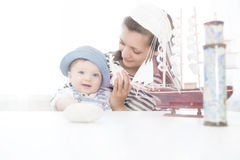 Travel concept. Mother and her baby boy with seashell. Stock Image