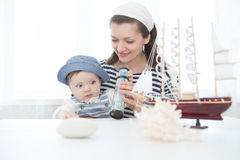 Travel concept. Mother and her baby boy with seashell. Travel concept. Mother and her baby boy listening sounds of the sea in a seashell. Mother and son in sea Stock Images