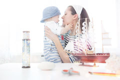 Travel concept. Mother and her child boy making model ship. Stock Image