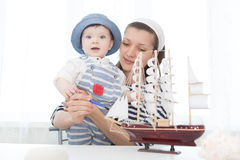 Travel concept. Mother and her child boy making model ship. Stock Photography