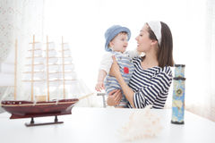 Travel concept. Mother and her child boy making model ship. Royalty Free Stock Images