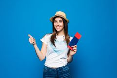 Travel concept portrait of smiling woman holding passport with ticket showing thumb up on blue background. Travel concept portrait of smiling woman holding Stock Photo